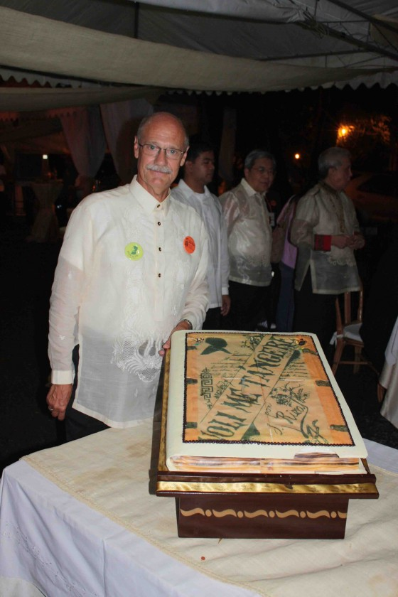 Lucien Spittael at the celebration of Rizal's sesquicentennial at Fort Santiago. He is standing by a cake modeled on the Noli Me Tangere.
